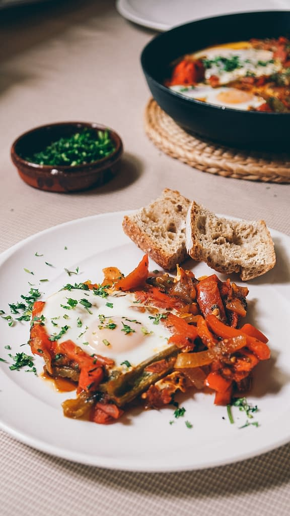fried eggs with vegetables, parsley and toasted bread