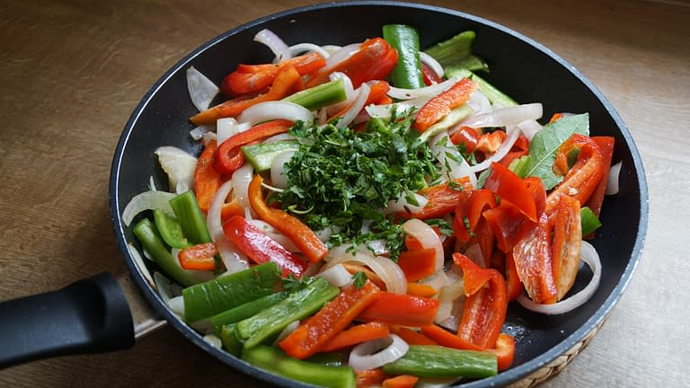 onions and bell peppers frying in a pan with parsley on top
