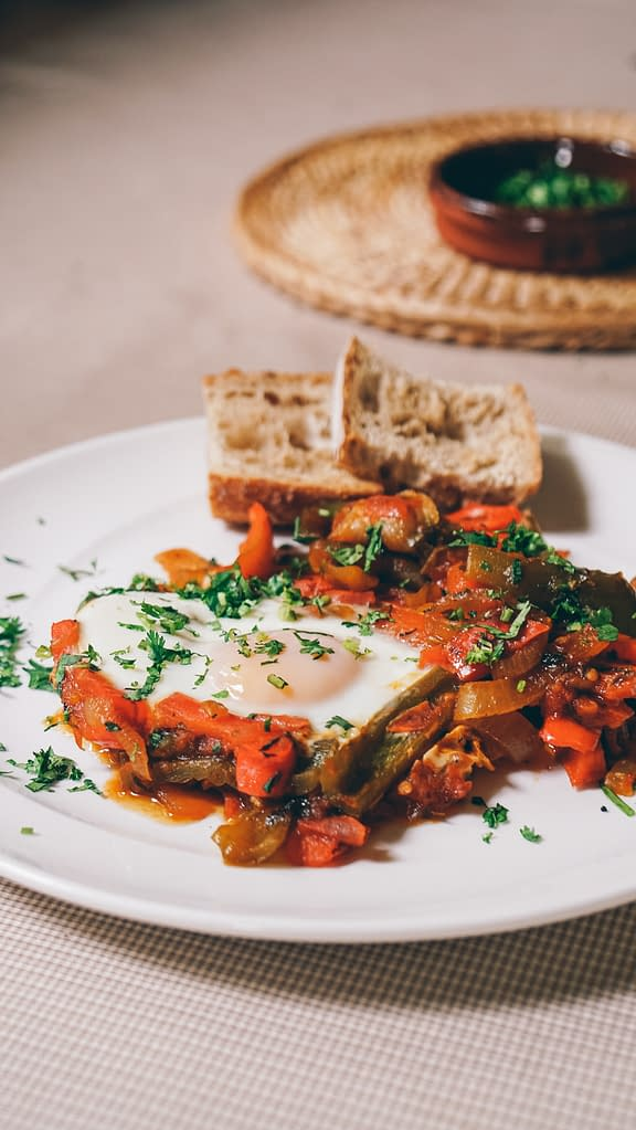 fried eggs with vegetables, parsley and toasted bread in a plate
