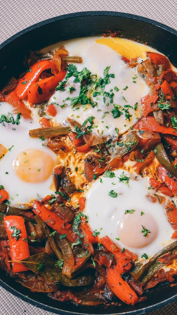 fried eggs with vegetables in a pan