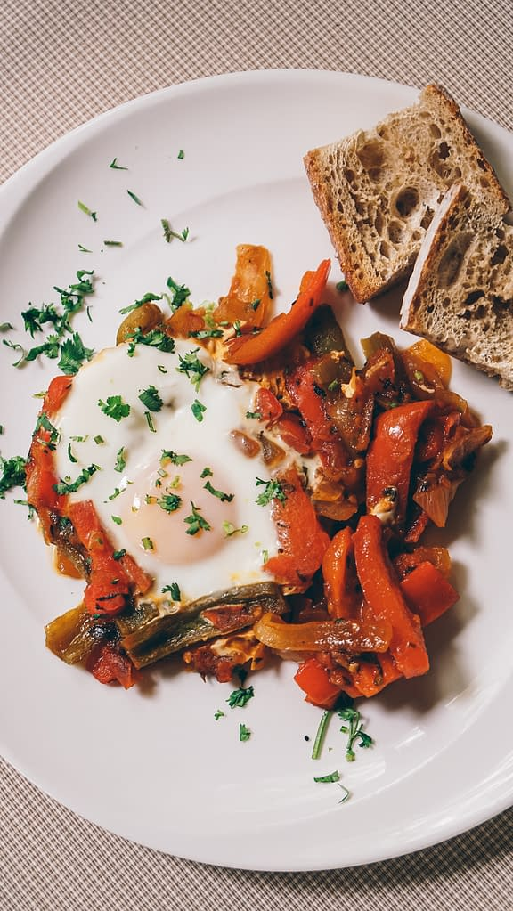 fried eggs with vegetables parsley and toasted bread