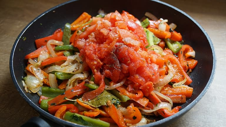 vegetables frying in a pan with crushed tomatoes